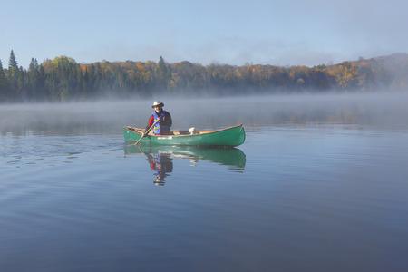 Man paddling a Green Canoe on a Misty Autumn Lake - Ontario, Canada photo