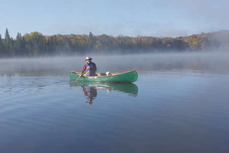 Man paddling a Green Canoe on a Misty Autumn Lake - Ontario, Canada photo