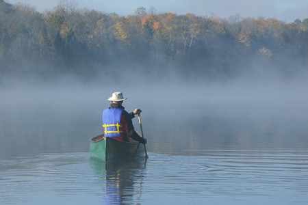 Canoeist Paddling a Green Canoe on a Misty Autumn Lake - Ontario, Canada photo