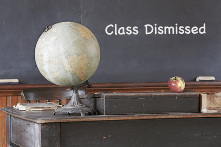 schoolhouse: Class Dismissed message on blackboard in old vintage schoolhouse