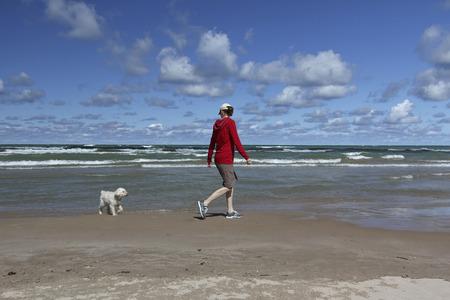 personas saludables: Mujer que recorre en una playa de Huron de lago con un peque�o perro blanco - Grand Bend, Ontario, Canad�
