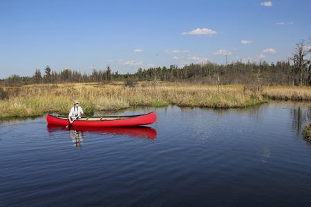 Birder Paddling a Canoe in the Okefenokee Swamp National Wildlife Refuge - Georgia
