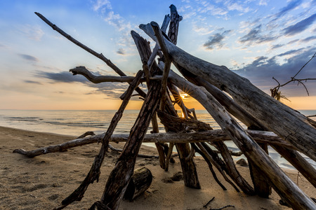 pinery: The sun sets behind a leanto built from driftwood on a a sandy beach in Pinery Provincial Park - Ontario, Canada