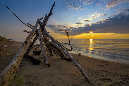 pinery: The sun sets behind a lean-to built from driftwood on a sandy beach in Pinery Provincial Park - Ontario, Canada