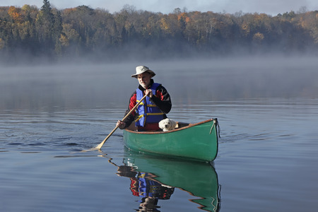 small white dog: Man Paddling a Canoe on a Lake in Autumn with a Small White Dog in the Bow - Ontario, Canada Stock Photo