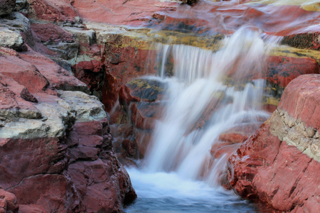 north cascade national park: Stream Cascading Through a Canyon Carved in Red Granite Rock - Waterton Lakes National Park, Alberta, Canada