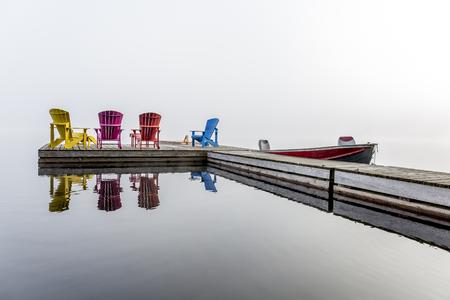 muskoka: Colorful Muskoka Chairs Arranged on a Dock with a Small Motorboat on a Misty Morning - Haliburton, Ontario, Canada Stock Photo