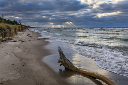 pinery: Shafts of sunlight poke out from behind autumn storm clouds on a Lake Huron beach - Pinery Provincial Park, Ontario, Canada