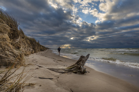 pinery: Man running on a Lake Huron beach at sunset as the suns rays poke thorugh some clouds - Pinery Provincial Park, Ontario, Canada