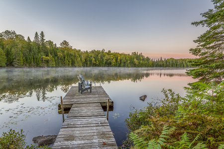 adirondack: Dock with Adirondack Chairs at Sunset on a Lake in Ontario, Canada Stock Photo