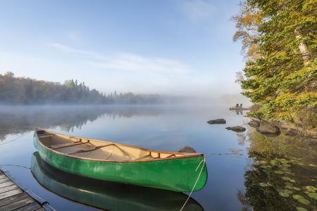 Green Canoe Gebonden aan dok op een meer in de herfst - Ontario, Canada Stockfoto