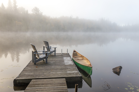 muskoka: A green canoe tied to a wooden dock with a pair of empty Adirondack chairs - Haliburton Highlands, Ontario, Canada