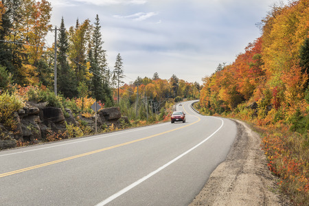 curve road: Red Car Driving on a Winding Road Surrounded by Fall Color - Algonquin Provincial Park, Ontario, Canada