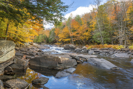 Oxtongue River in autumn with vibrant fall colors reflecting on its surface - Ontario, Canada