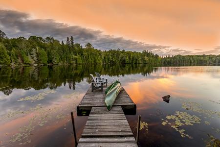 silla de madera: Canoa verde y sillas en un muelle junto a un lago en la puesta del sol - montañas de Haliburton, Ontario, Canadá