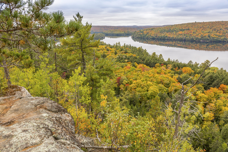 provincial forest parks: Lookout from a rocky outcrop over a lake surrounded by fall forest - Algonquin Provincial Park, Ontario, Canada