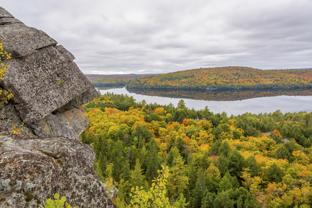 provincial forest parks: Outcrop of Precambrian rock in autumn with a forested lake in the distance - Algonquin Provincial Park, Ontario, Canada