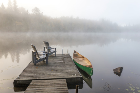 adirondack: A green canoe tied to a wooden dock with a pair of empty Adirondack chairs - Haliburton Highlands, Ontario, Canada