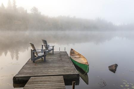 Een groene kano vastgebonden aan een houten dok met een paar lege Adirondack stoelen - Haliburton Highlands, Ontario, Canada
