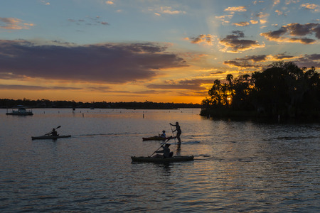 Kayakers en Paddle Boarder Silhouetted bij Sunset-Crystal River, Florida