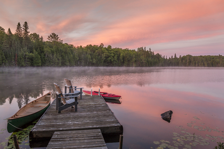 Canoe and kayak moored to a cottage dock at dawn - Ontario, Canada 스톡 콘텐츠