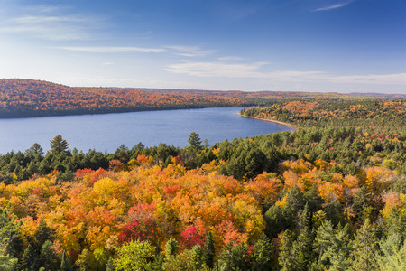 Overlooking a lake surrounded by brilliant fall foliage - Algonquin Provincial Park, Ontario, Canada 스톡 콘텐츠