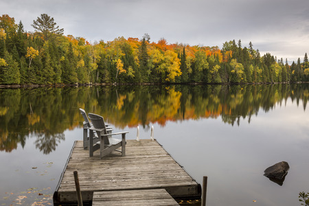 A pair of empty chairs sit on a dock on an autumn lake - Ontario, Canada Imagens