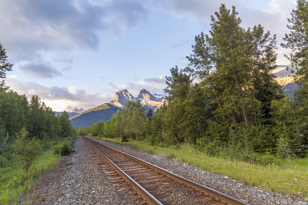 canmore: Railway tracks running through a boreal forest with the Rocky Mountains in the background - Canmore, Alberta
