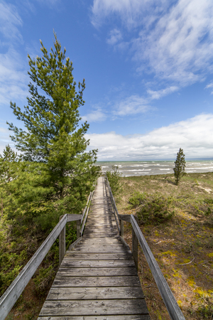 A boardwalk traverses a sensitive Lake Huron dune ecosystem, protecting the vegetation and providing easy access to the beach - Grand Bend, Ontario