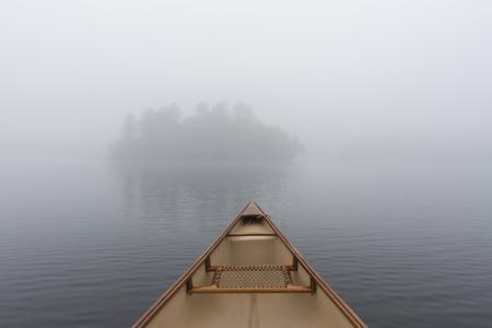 온타리오, 캐나다에서 호수에 섬쪽으로 얕은 동안 안개 낀 아침에 카누 활 스톡 콘텐츠