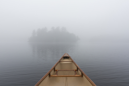 Canoe bow on a misty morning while paddling towards an island on a lake in Ontario, Canada