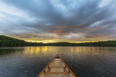 Kanoboog op een meer van Ontario bij zonsondergang - Canada