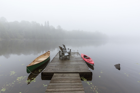 Canoe and kayak tied to a dock on a misty morning on a lake in Ontario, Canada Imagens