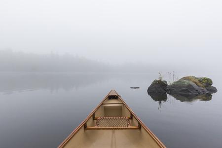 オンタリオ州、カナダの湖に霧の深い朝カヌー弓