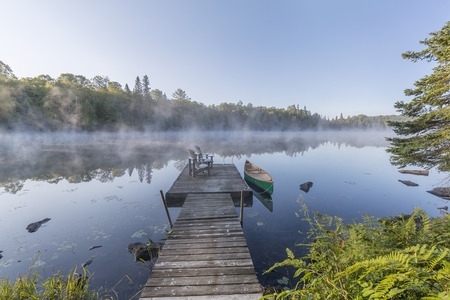 Green canoe tied to a dock on a misty morning - Ontario, Canada Imagens