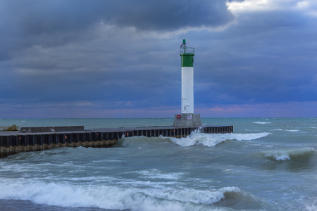Lighthouse and pier on Lake Huron with storm clouds passing over - Grand Bend, Ontario, Canada