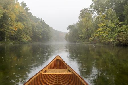 Bow of a cedar canoe on a river during a light rain - Ontario, Canada