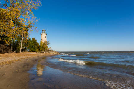 The historic Pelee Island Lighthouse, built in 1833, reflecting on its Lake Erie shoreline in autumn - Ontario, Canada