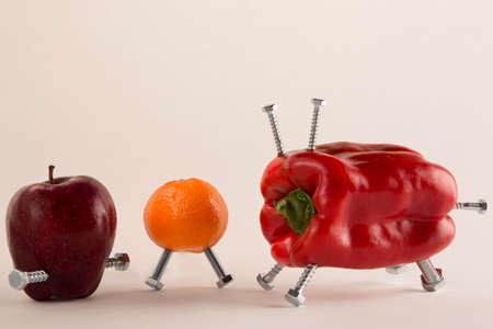 genetically modified: Pepe, mela e mandarino con bulloni una metafora sul cibo geneticamente modificato Archivio Fotografico