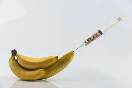 impotence: Male impotence metaphor: syringe with pills injecting into a  big banana among small bananas Stock Photo