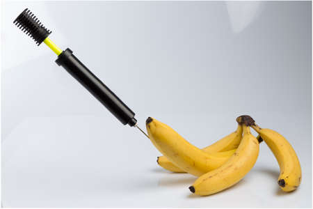 impotence: Male impotence metaphor: bicycle air pump pumping a  big banana among small bananas