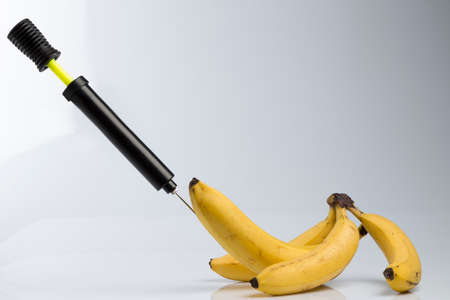 Male impotence metaphor: bicycle air pump pumping a  big banana among small bananas