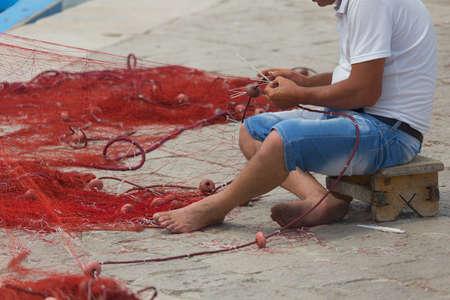 Fisherman repairs his net in Gallipoli (Le)