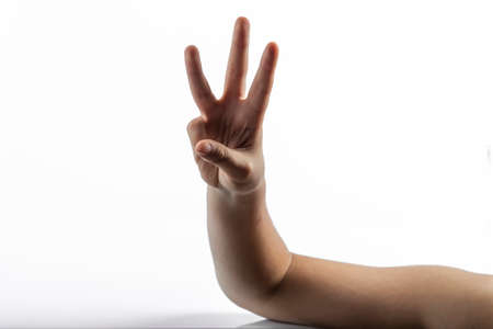 middlefinger: Young hands makes a gesture: number three sign with 3 fingers Stock Photo