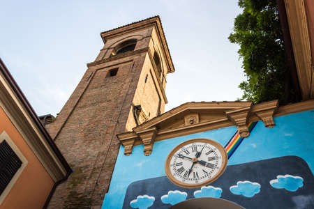 Steady works painted on the wall of the houses in the medieval small village of Dozza near Bologna in Emilia Romagna, Italy. Old clock in the middle. photo