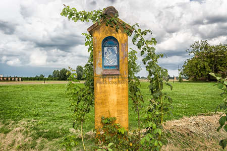 parish: Votive aedicula devoted to the Blessed Virgin Mary near the medieval countryside church of Campanile with romanesque cylindrical bell tower, located in the village of Santa Maria in Fabriago in Emilia Romagna region in northern Italy