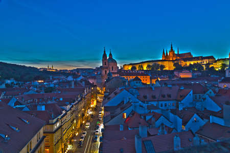 Night view of attractions in  Prague: St. Nicholas baroque church, Hradcany, the castle and St. Vitus Cathedral. Light traffics frames the buildings drawing regular lines