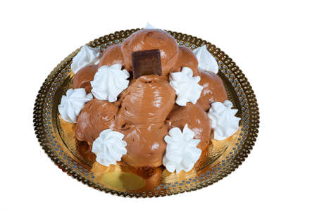 A dark chocolate topped profiterole cake according to Italian pastry with white cream in a pyramid shape photo