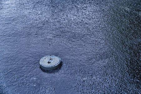 cast iron manhole cover in dark blue asphalt sea photo