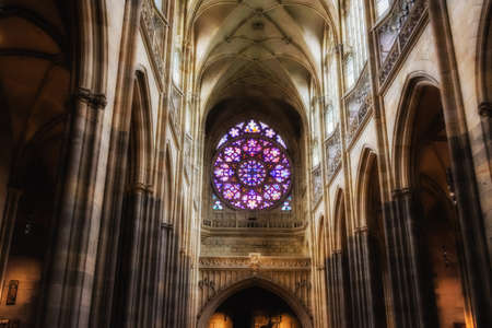 Decal window transparency of rosette among archs inside the cathedral of St Vitus in Prague, a church with dark Gothic towers guarded by gargoyle: the main religious symbol of the Czech Republic